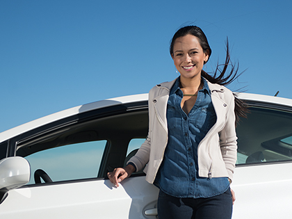 Latina woman standing next to a white car